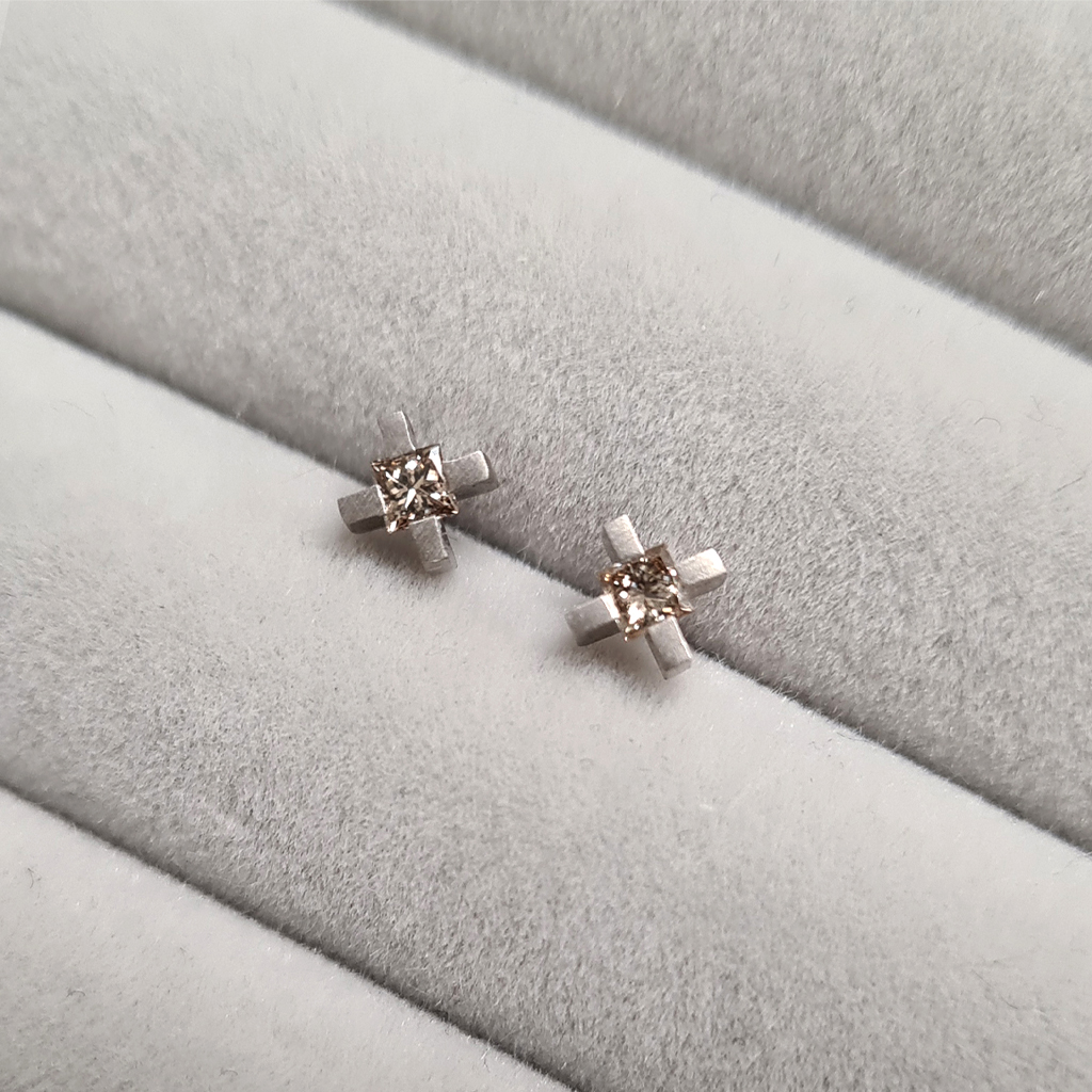micro xx earrings in white gold with champagne princess cut diamonds on a grey velvet tray.