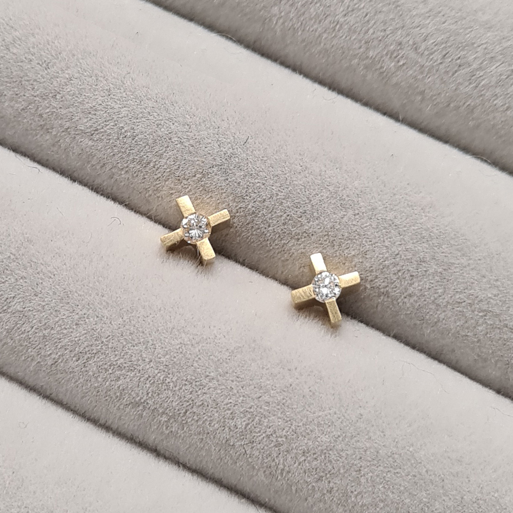 micro xx earrings in yellow gold with diamonds on a grey velvet tray.