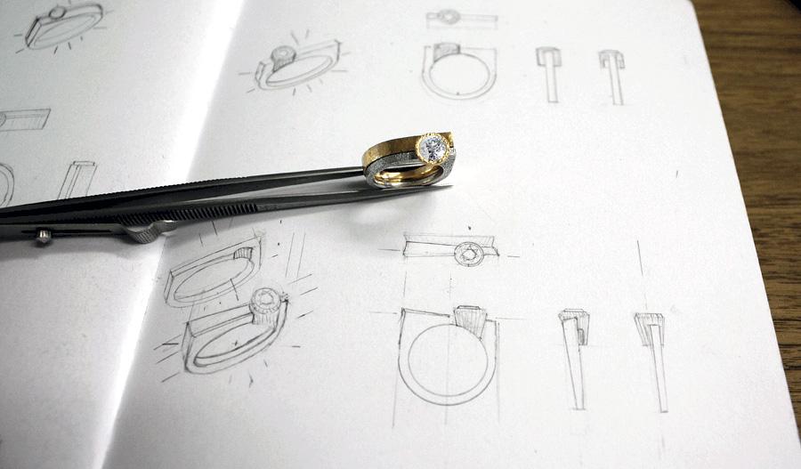 Pair of rings held in tweezers over hand drawn pencil sketches.