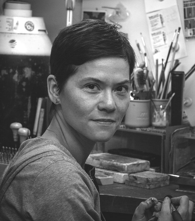 Black and white portrait of Amanda Li Hope sitting at her workbench in London, England.