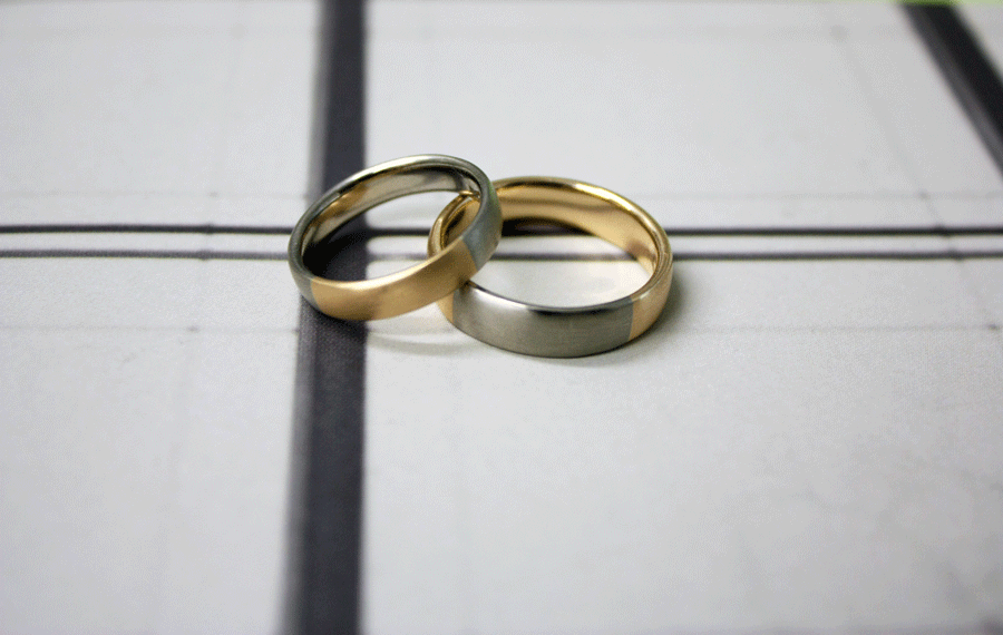 Two wedding rings in rose and white gold on a background of white paper with black lines.