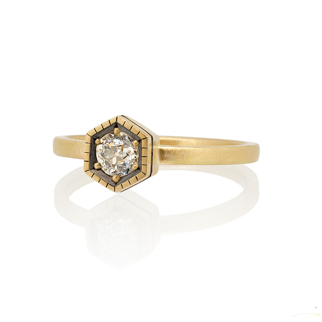 Old cut, diamond ring in yellow gold with hexagon shaped setting with black rhodium detailing on a white background.