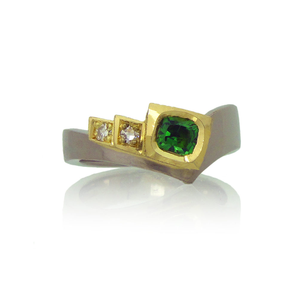 Front view of tsavorite and diamond ring on white background.