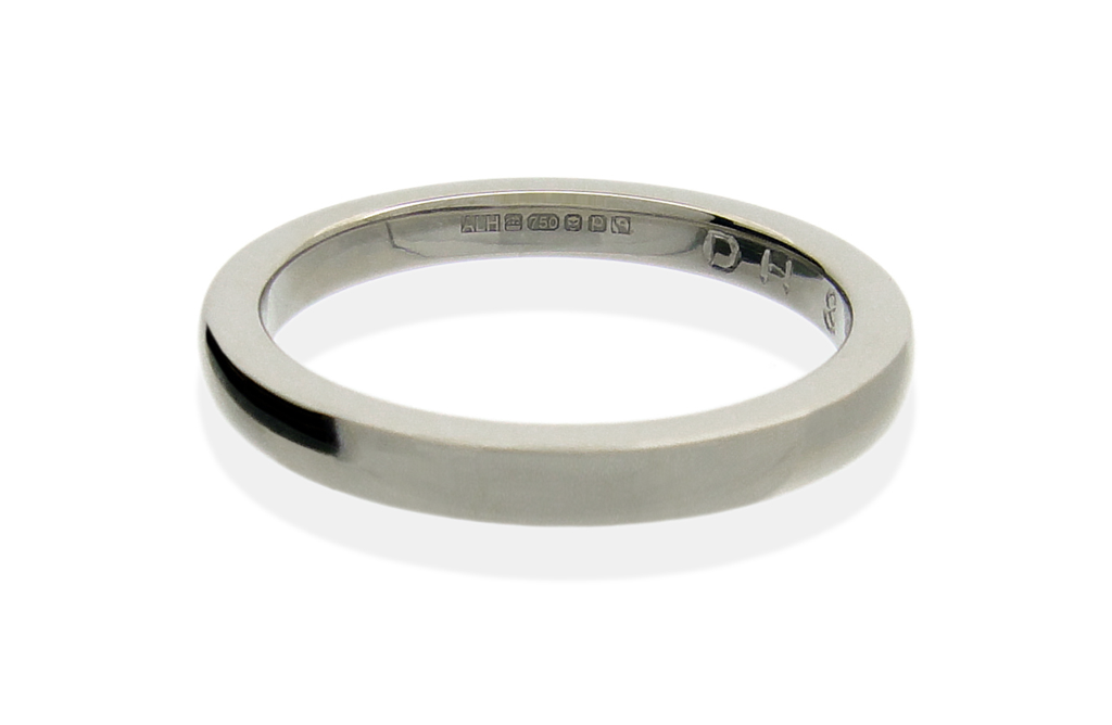 Ethical Fairtrade gold wedding rings with hand engraving on white background