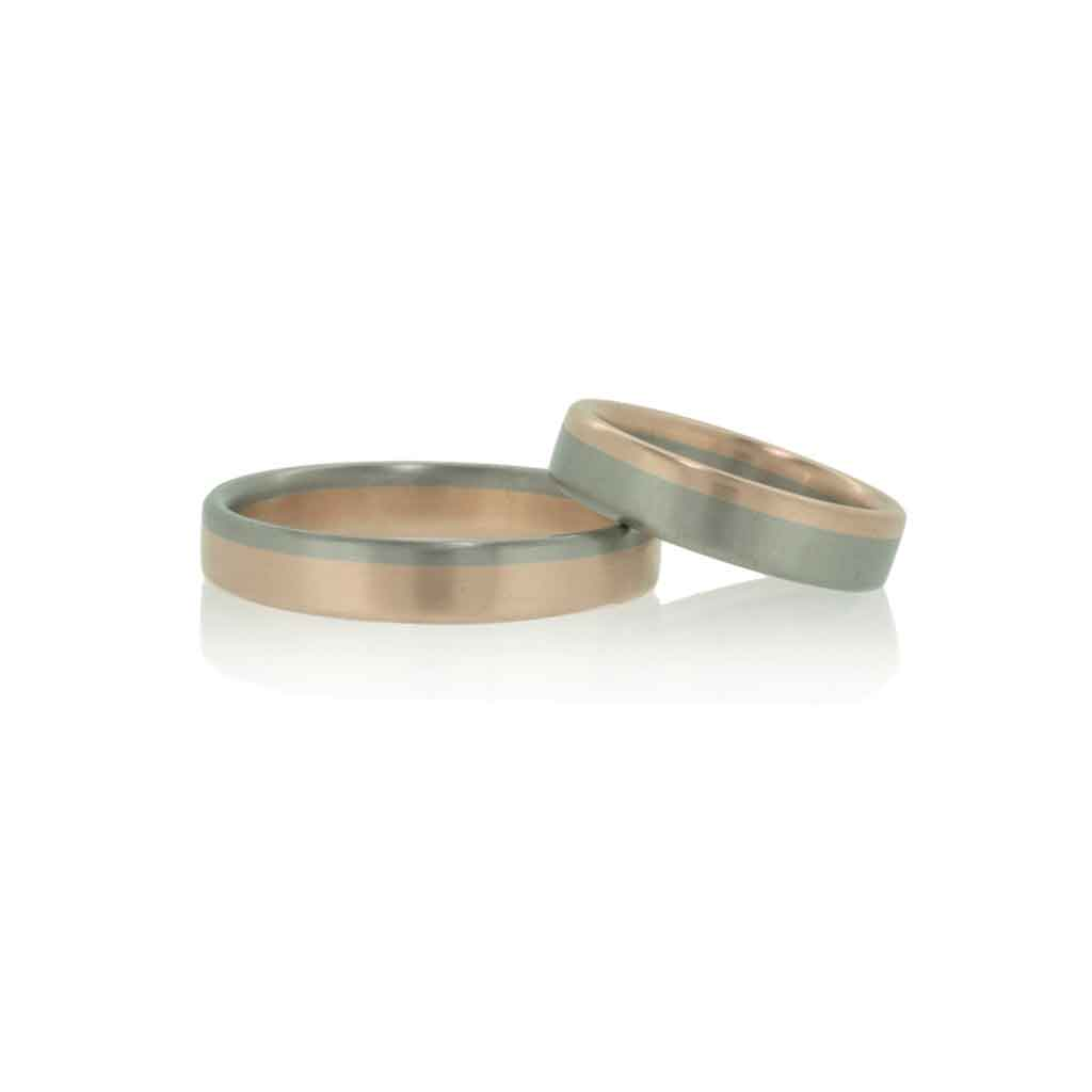 Two tone wedding rings in rose and white gold set against a white background.