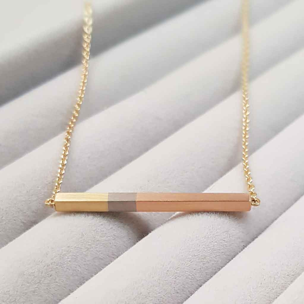Bar necklace in rose, white and yellow gold on a grey velvet background.