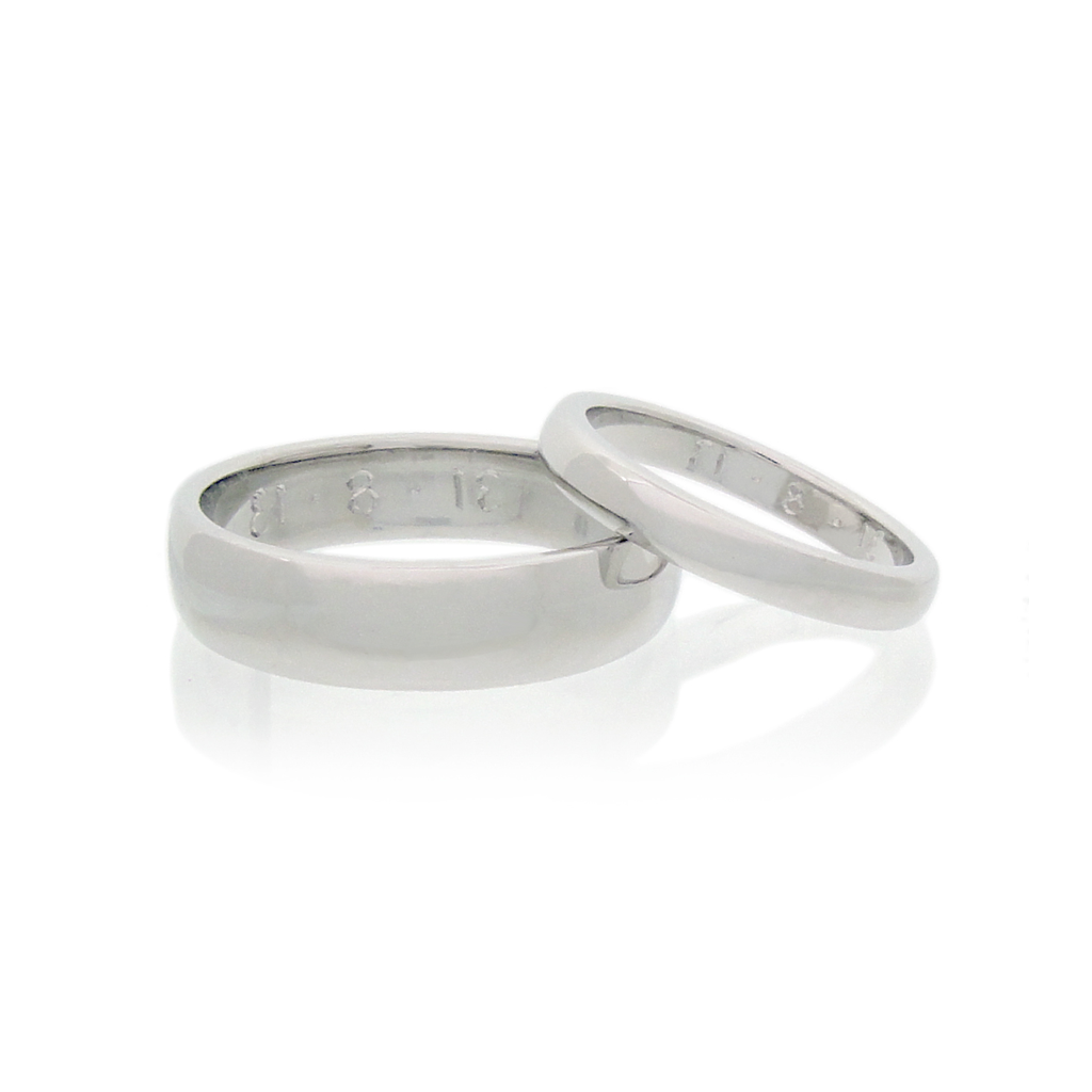 A pair of handmade wedding rings set against a white background.