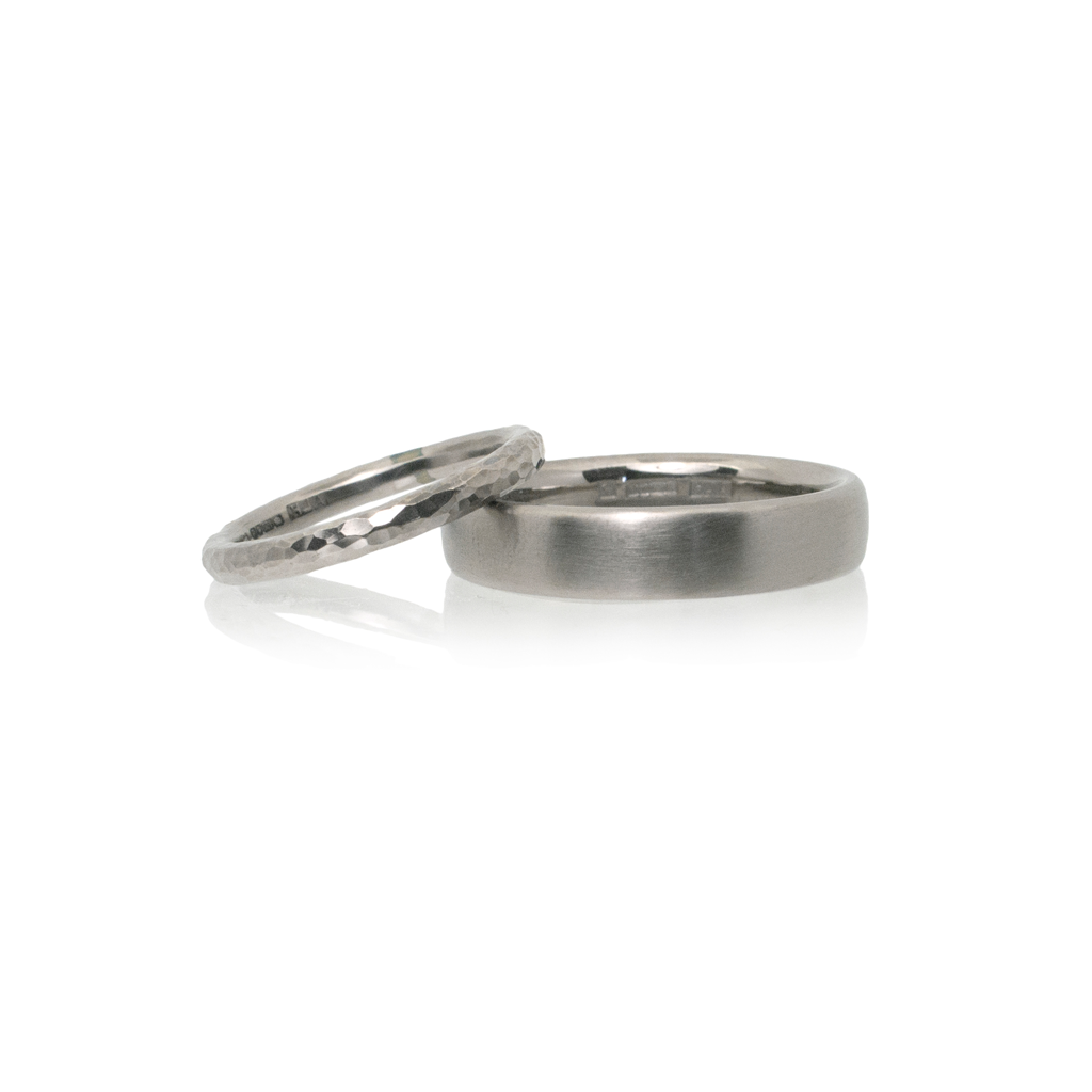 A pair of white gold wedding rings set against a white background.