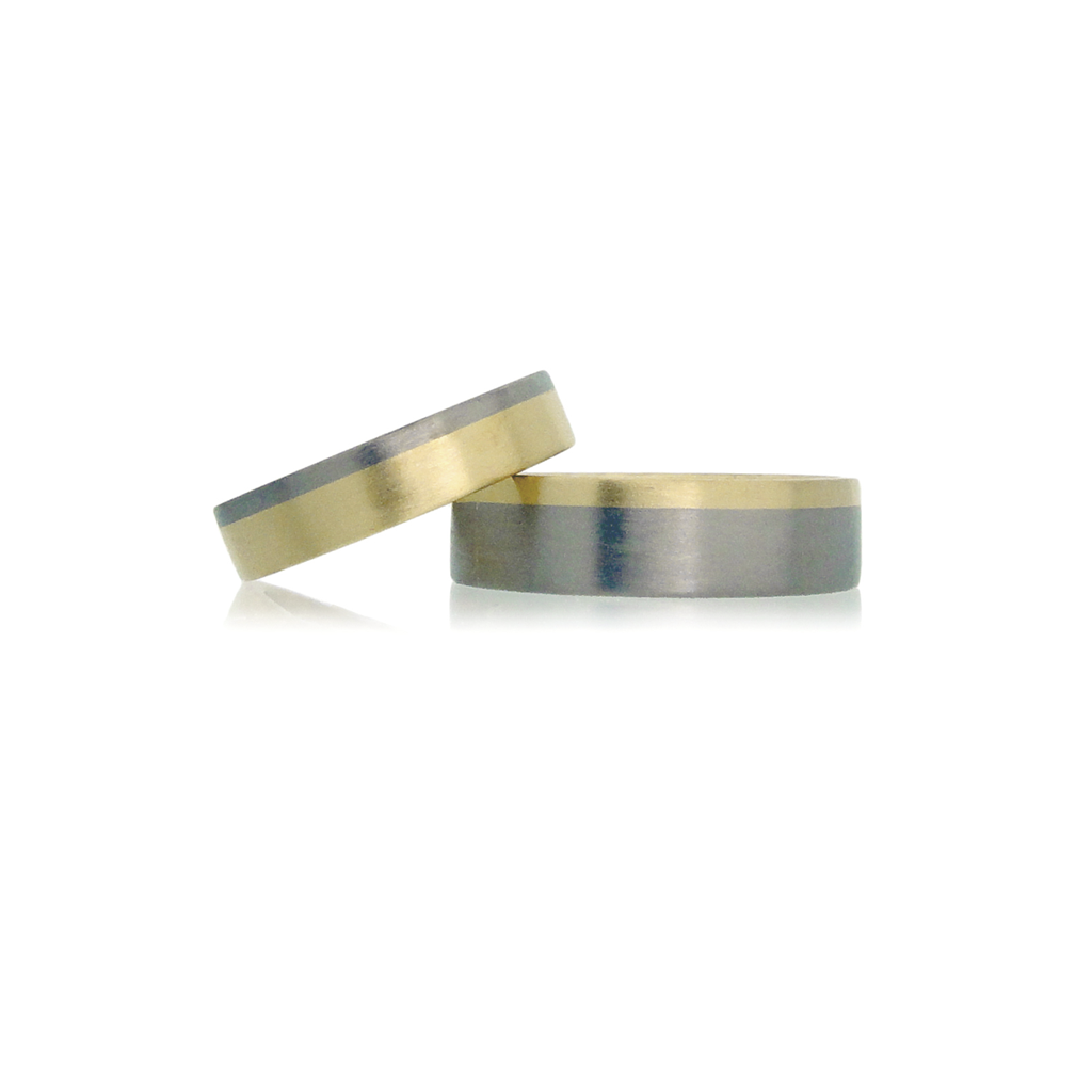 Two bi-metal wedding rings in yellow and white gold set against a white background.