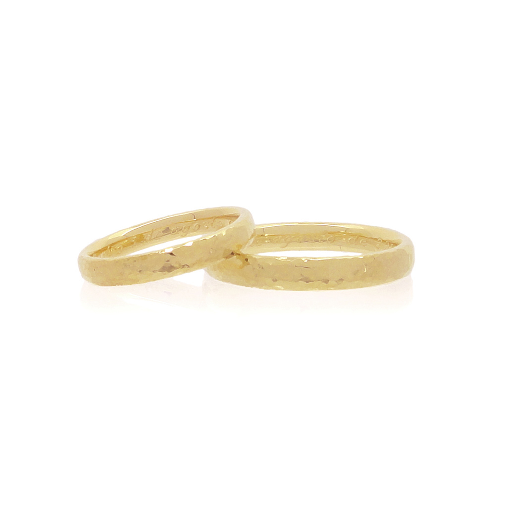 A pair of yellow gold wedding ring laying on a white background.
