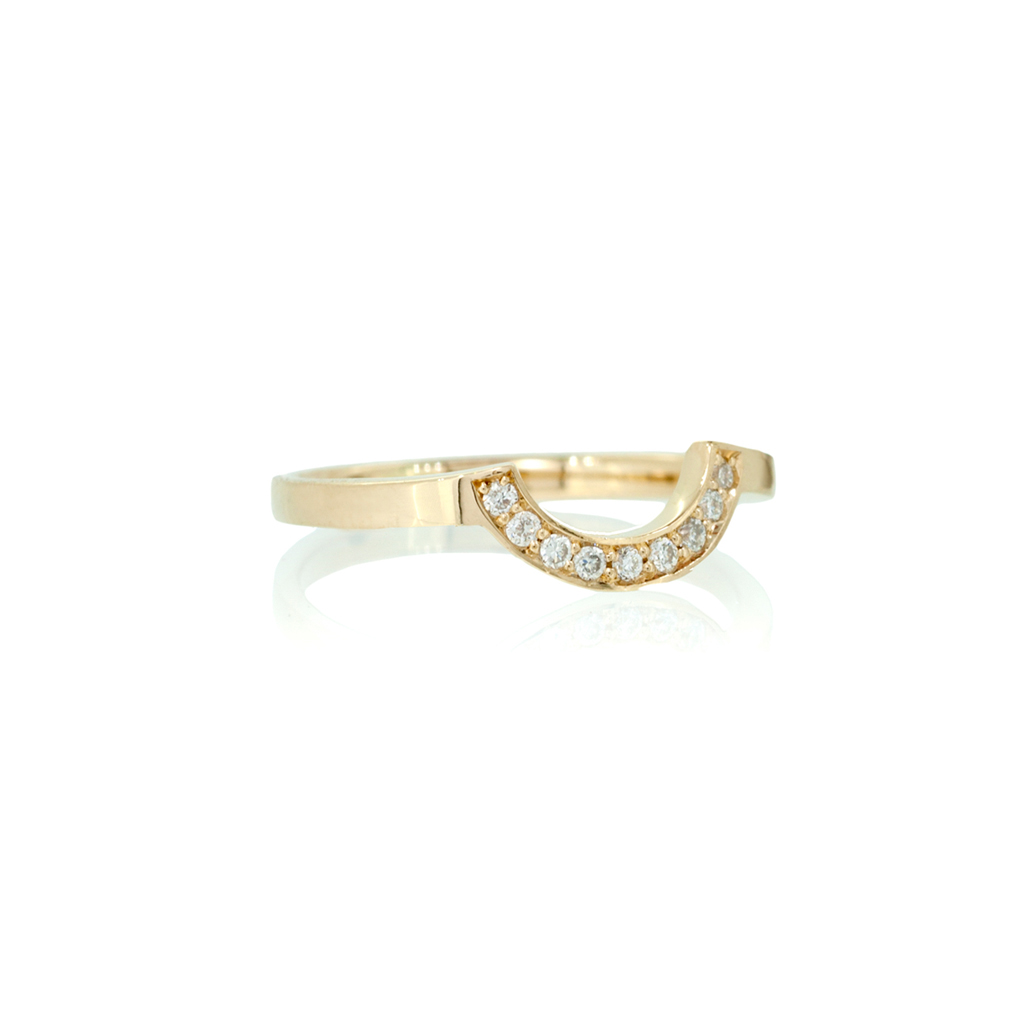 Shaped wedding band with diamonds set against a white background.