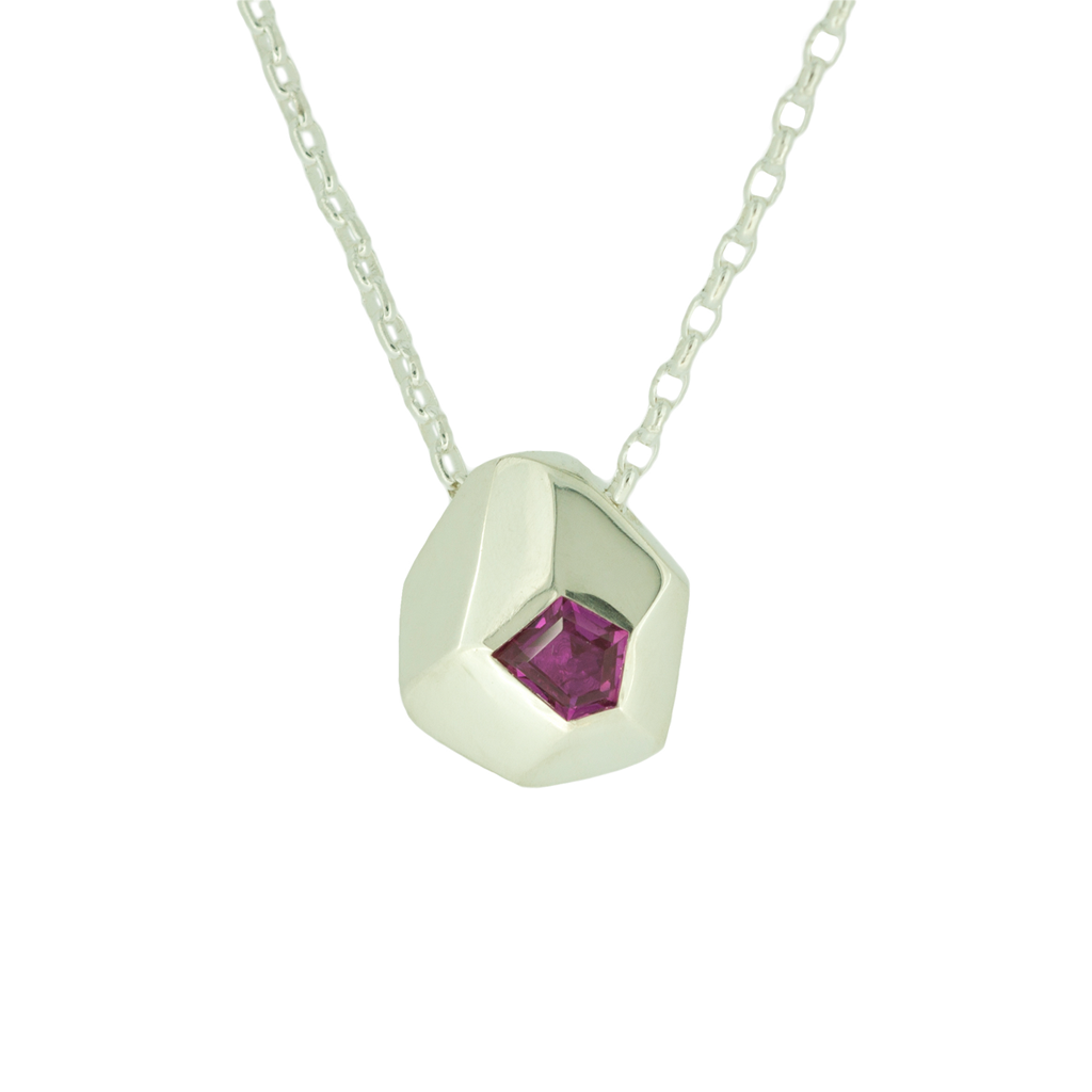 Contemporary silver pendant set with freeform ruby hanging on a white background.