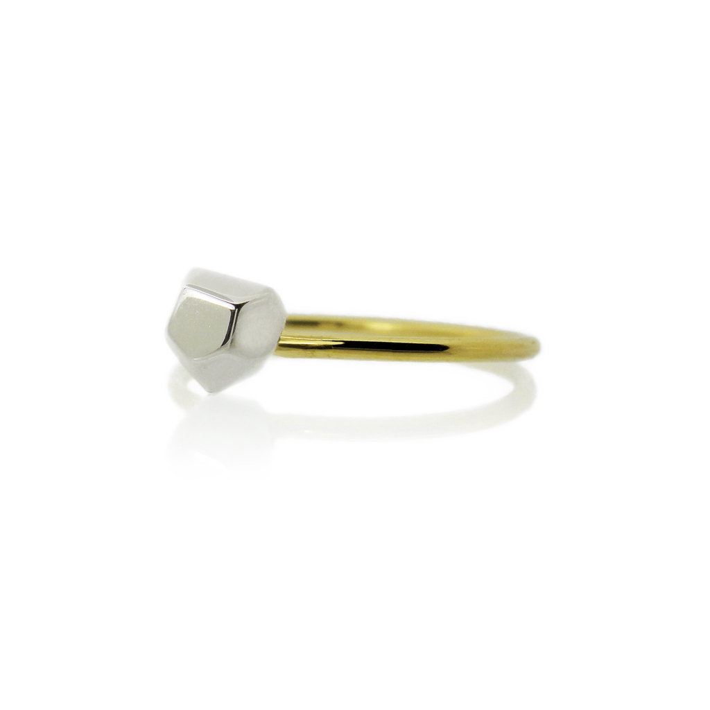 Asteroid solitaire ring. Asteroid in white gold, the band in yellow gold on a white background.