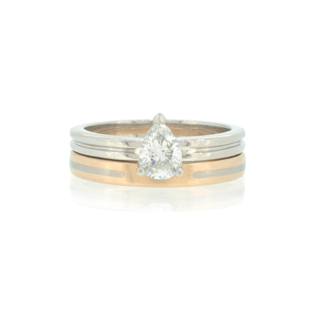 Engagement ring with pear cut diamond on top of bi-coloured wedding ring against a white background.