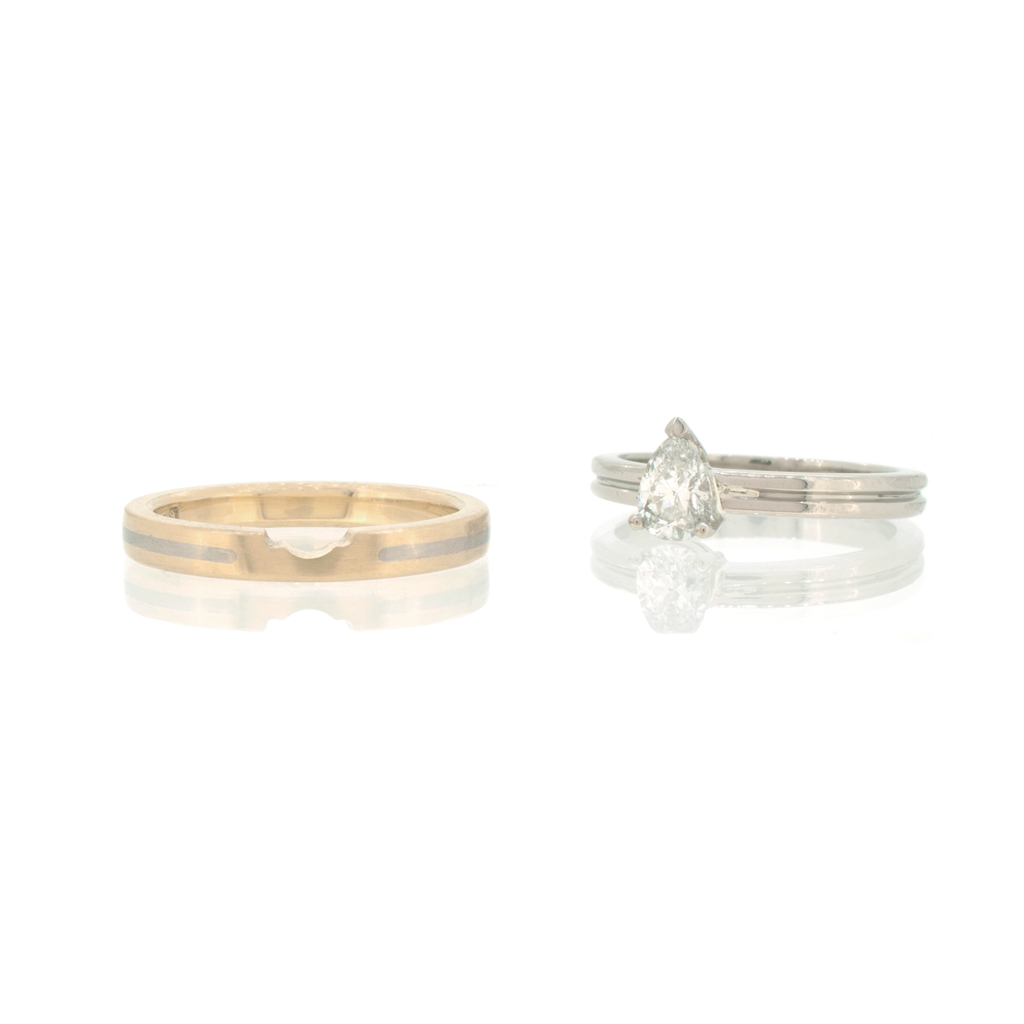 White and yellow gold notched wedding ring against a white background.