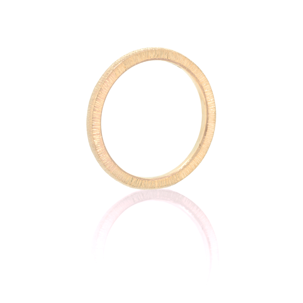 Woman's ring sitting upright on its edge on a white background.