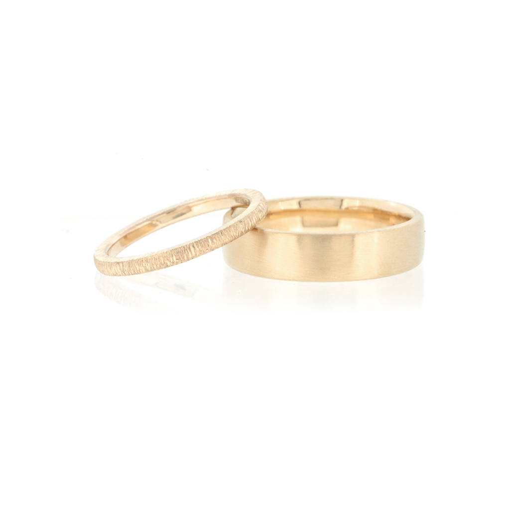 A pair of yellow gold wedding rings on a white background.