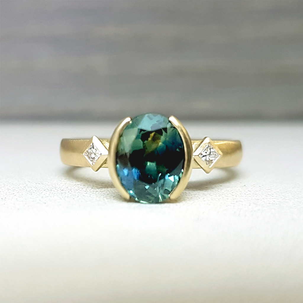 photo of sapphire ring on grey background