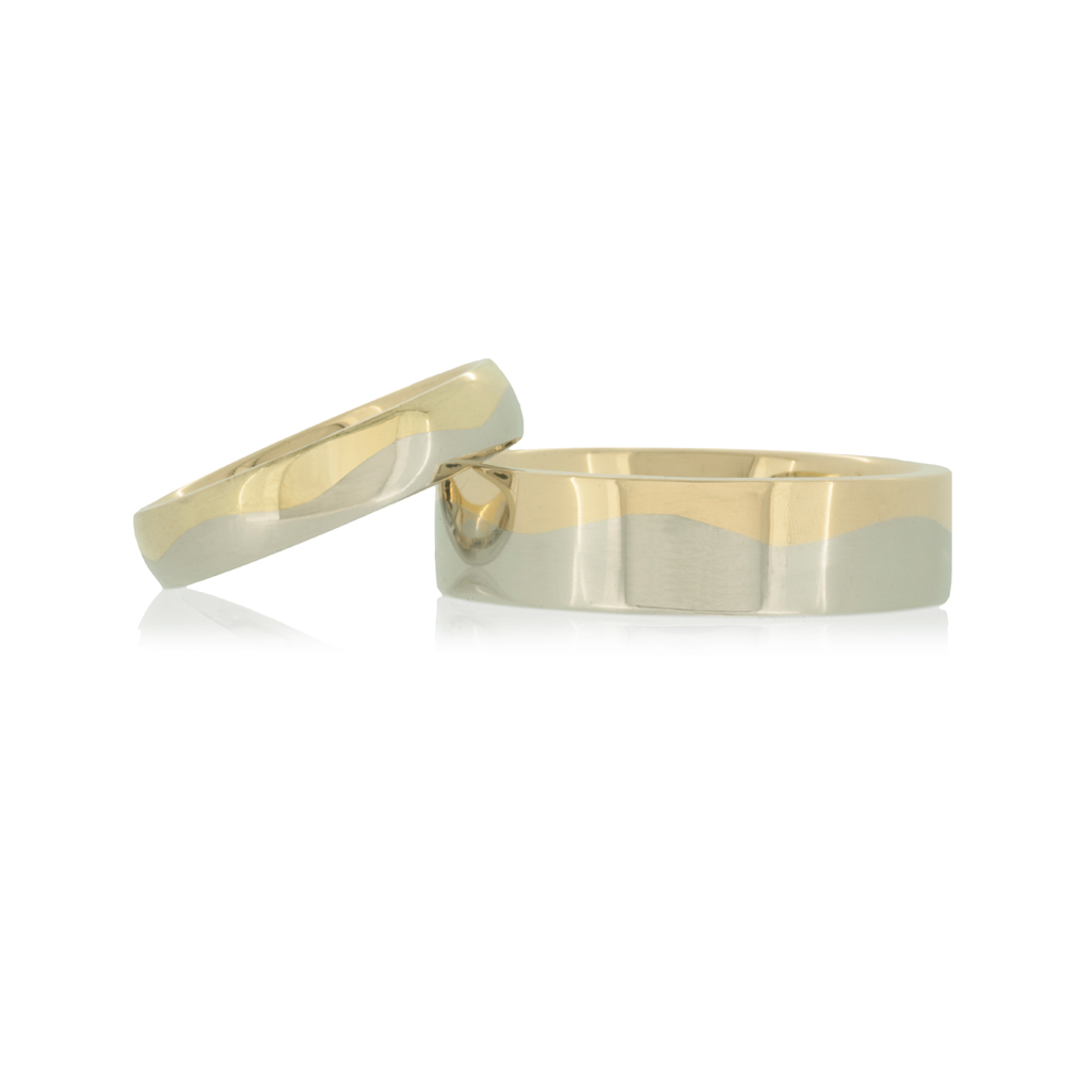 Yellow and platinum wedding rings with wave design set against a white background.