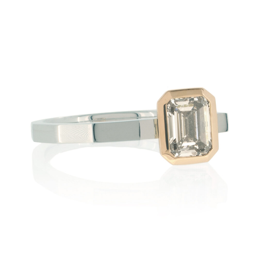 Emerald cut diamond ring in platinum and rose gold on a white background.