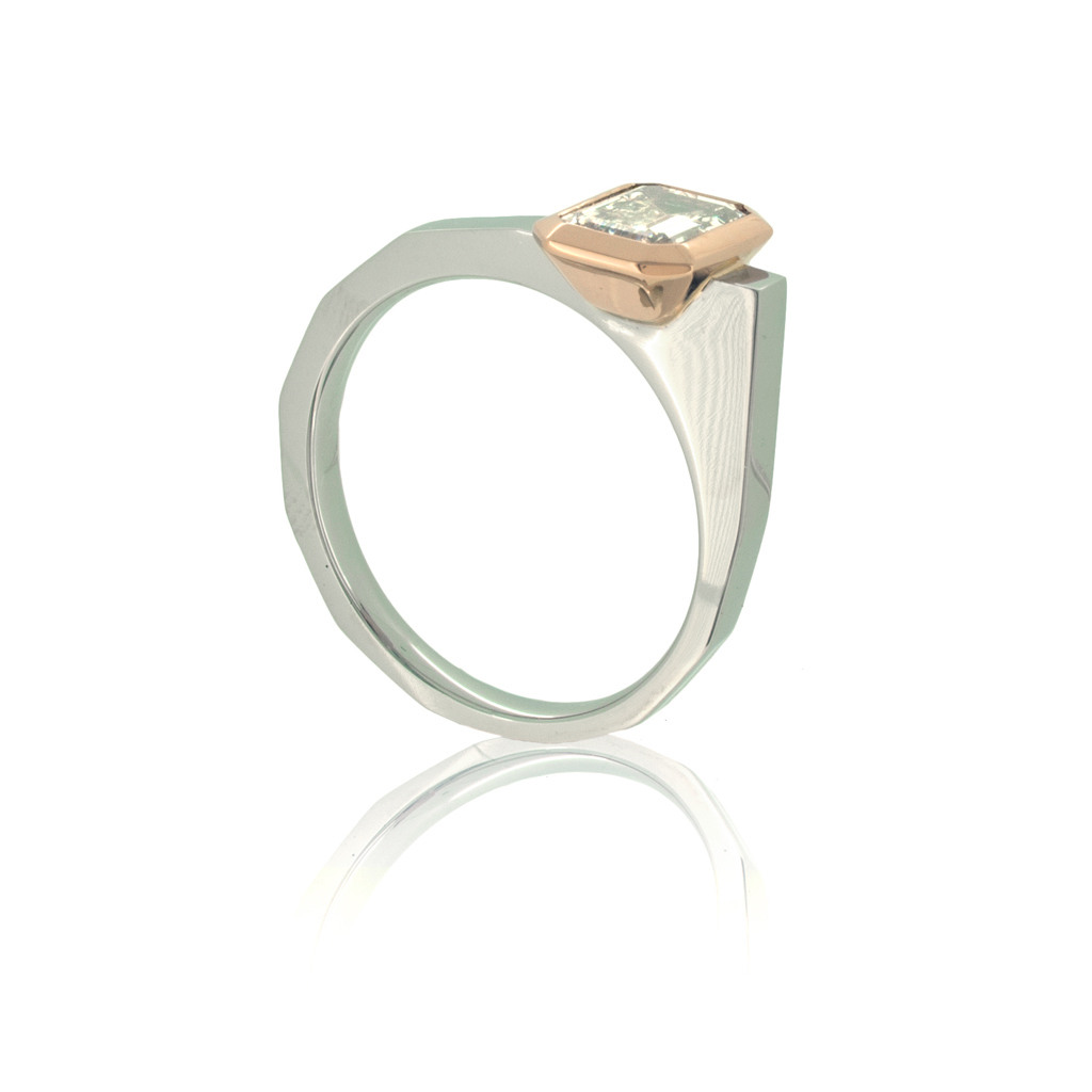 Emerald cut diamond ring in platinum and rose gold standing upright on a white background.