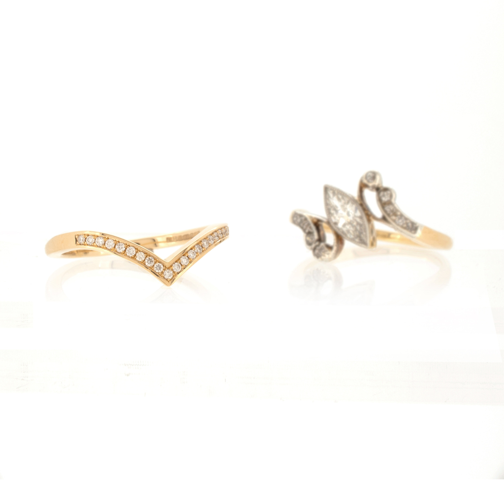 Diamond set V-shaped wedding band next to vintage engagement ring on white background.