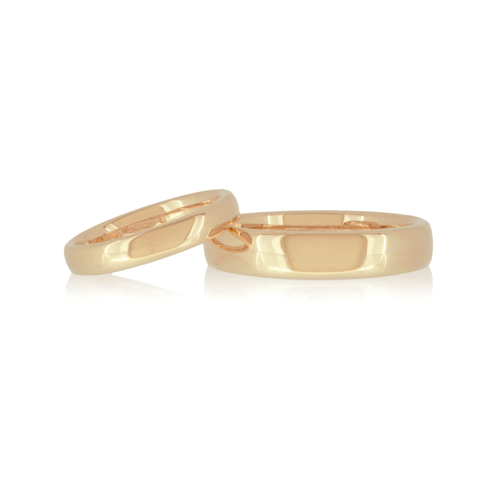 Two rose gold wedding rings on a white surface set against white background