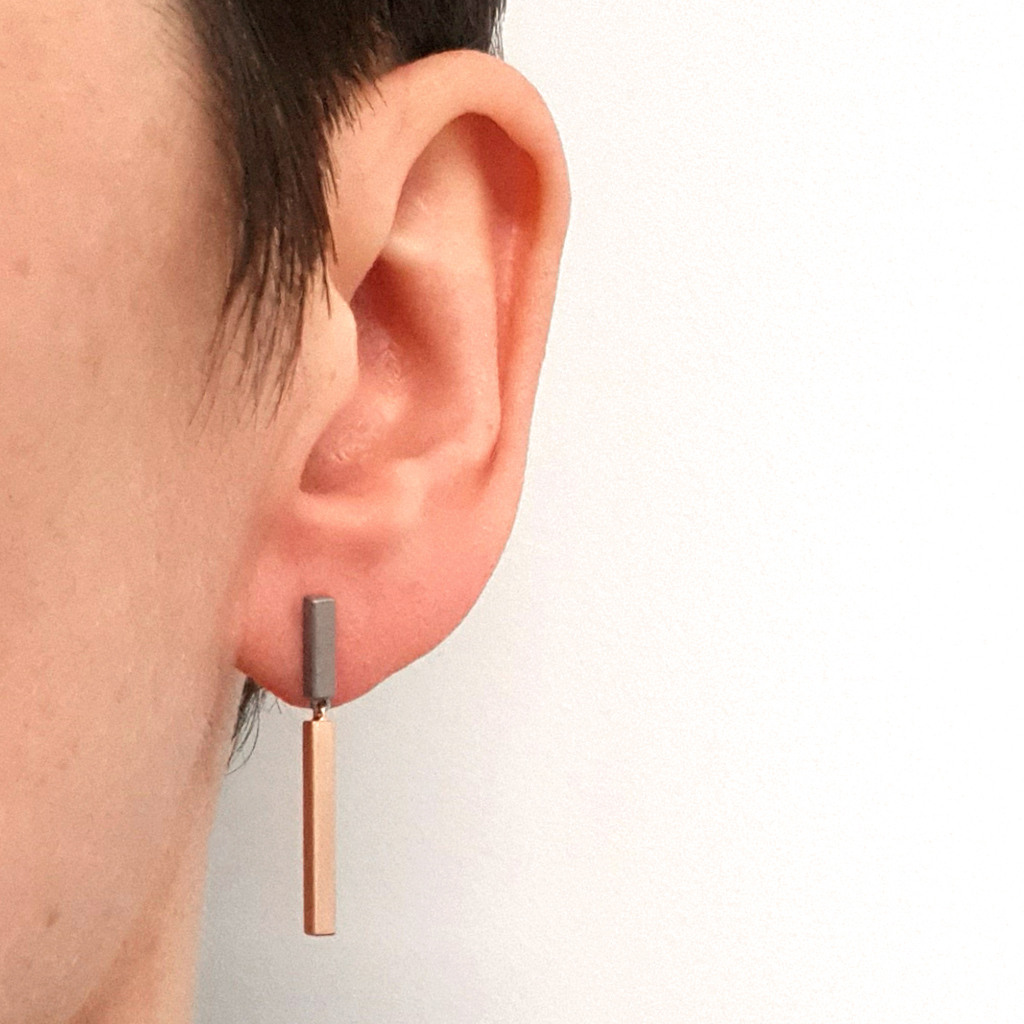Two tone bar earring hanging on a person's ear and with a white background.