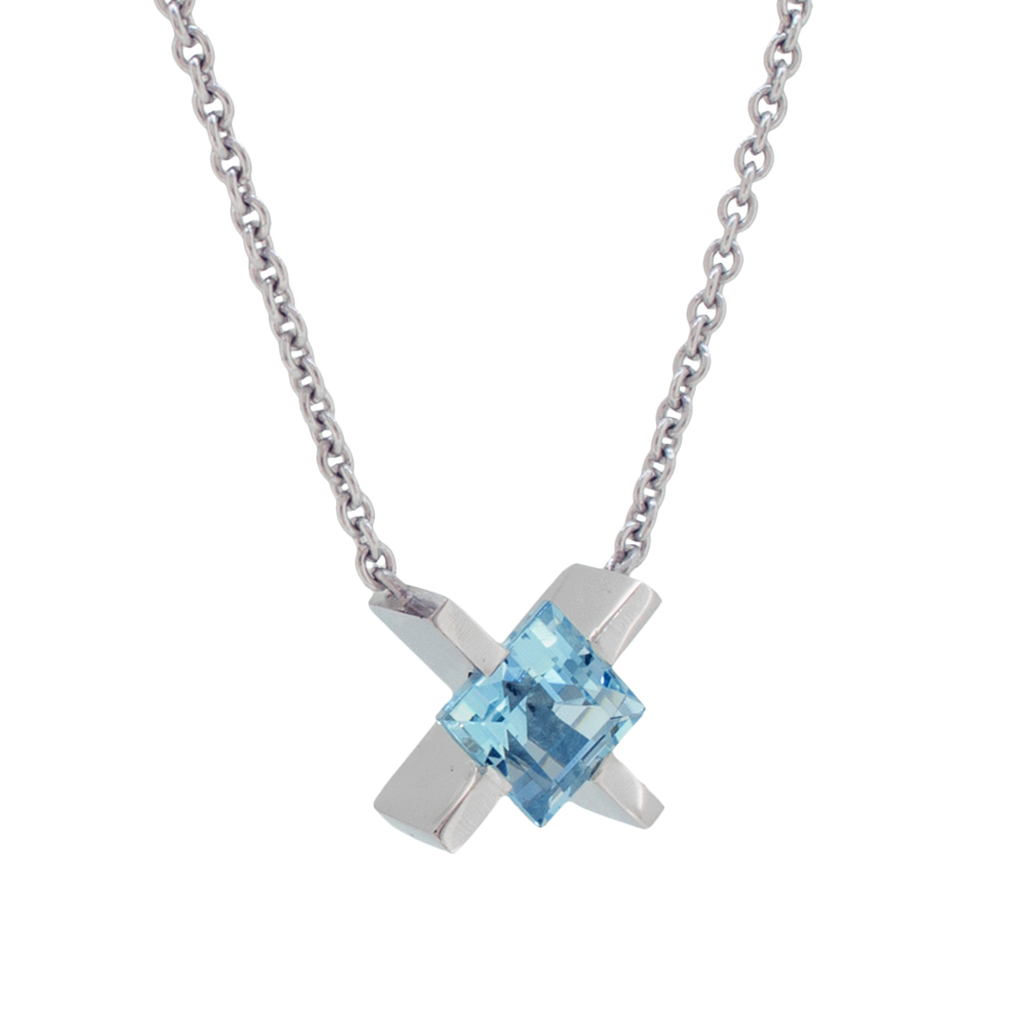 Platinum 'X' pendant with a square cut aquamarine hanging on a chain in front of a white background.
