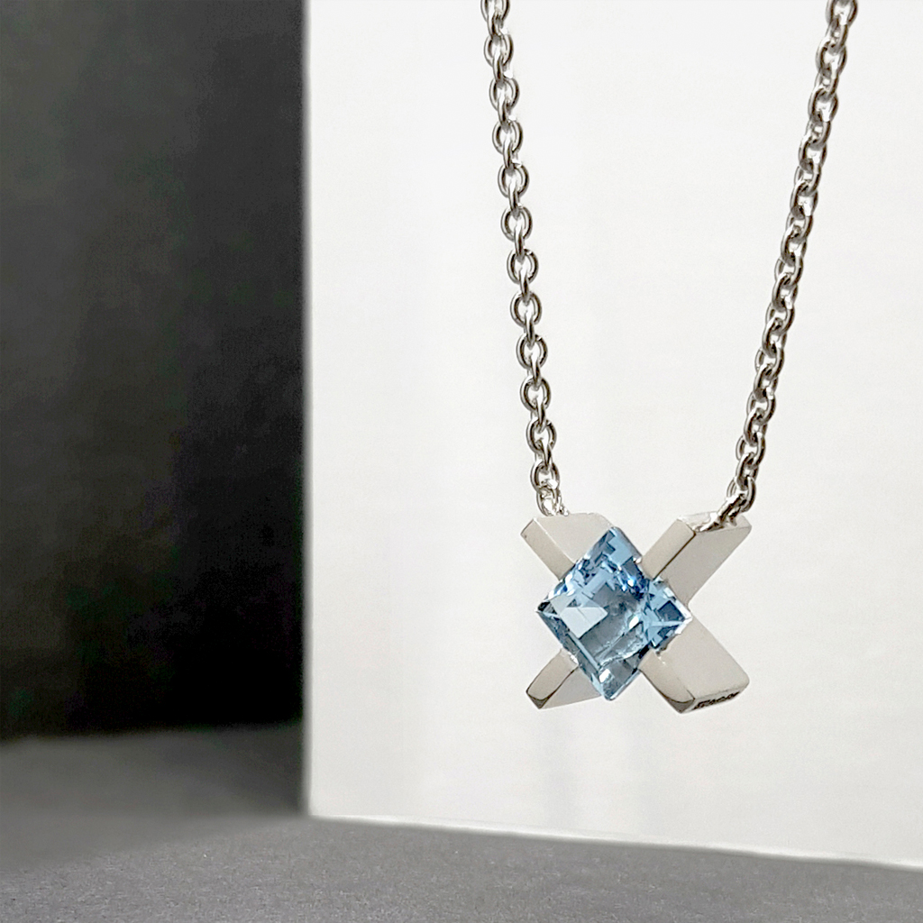 Platinum 'X' pendant with a square cut aquamarine hanging on a chain in front of a black and white background.