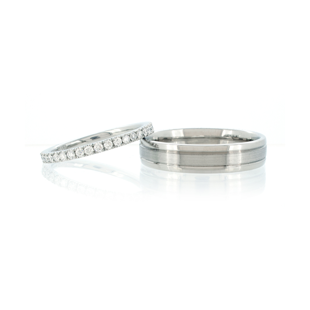 Diamond eternity ring and men's wedding ring with two groove set against a white background.