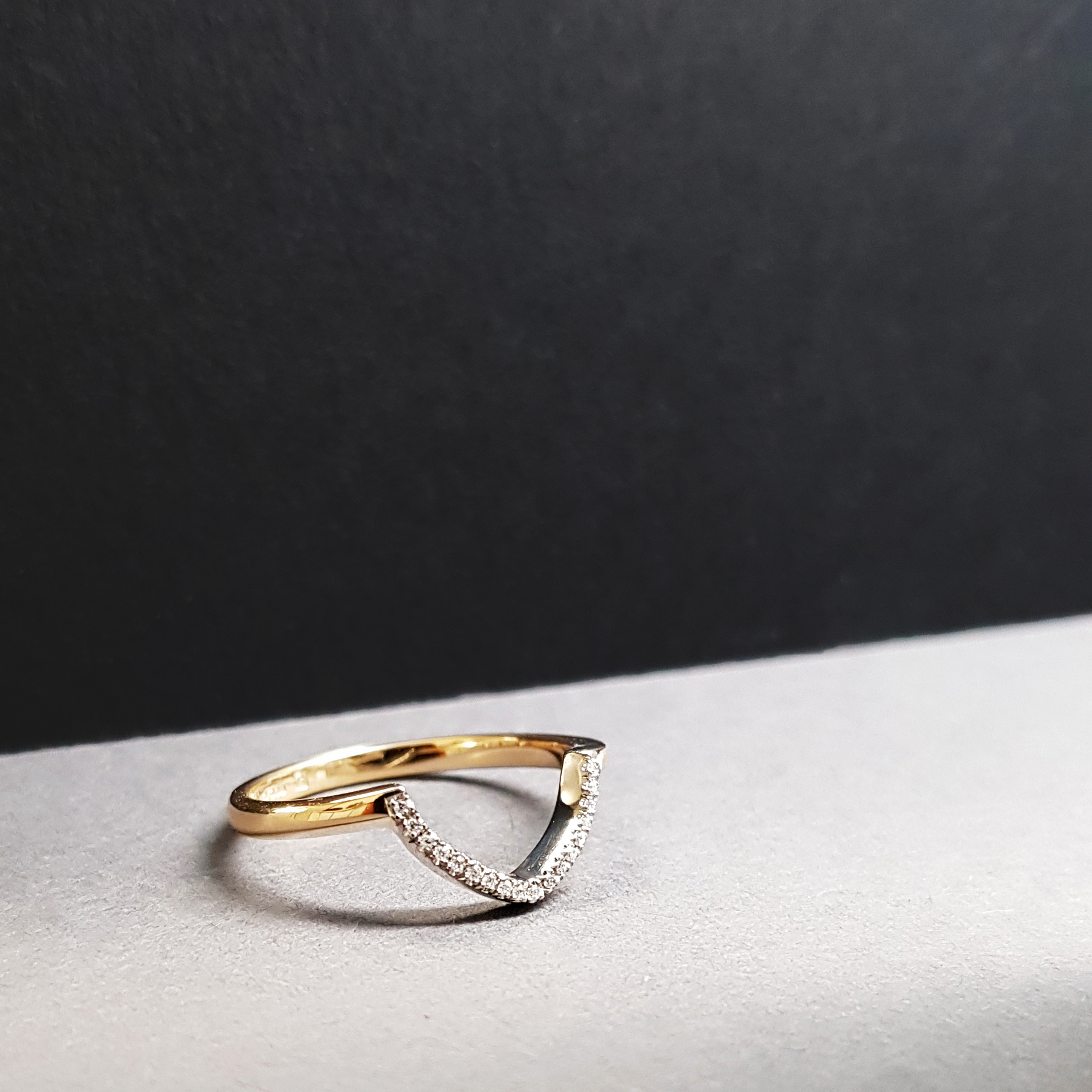 V-shaped diamond wedding ring dramtically lit and sitting on a white surface with a black background.