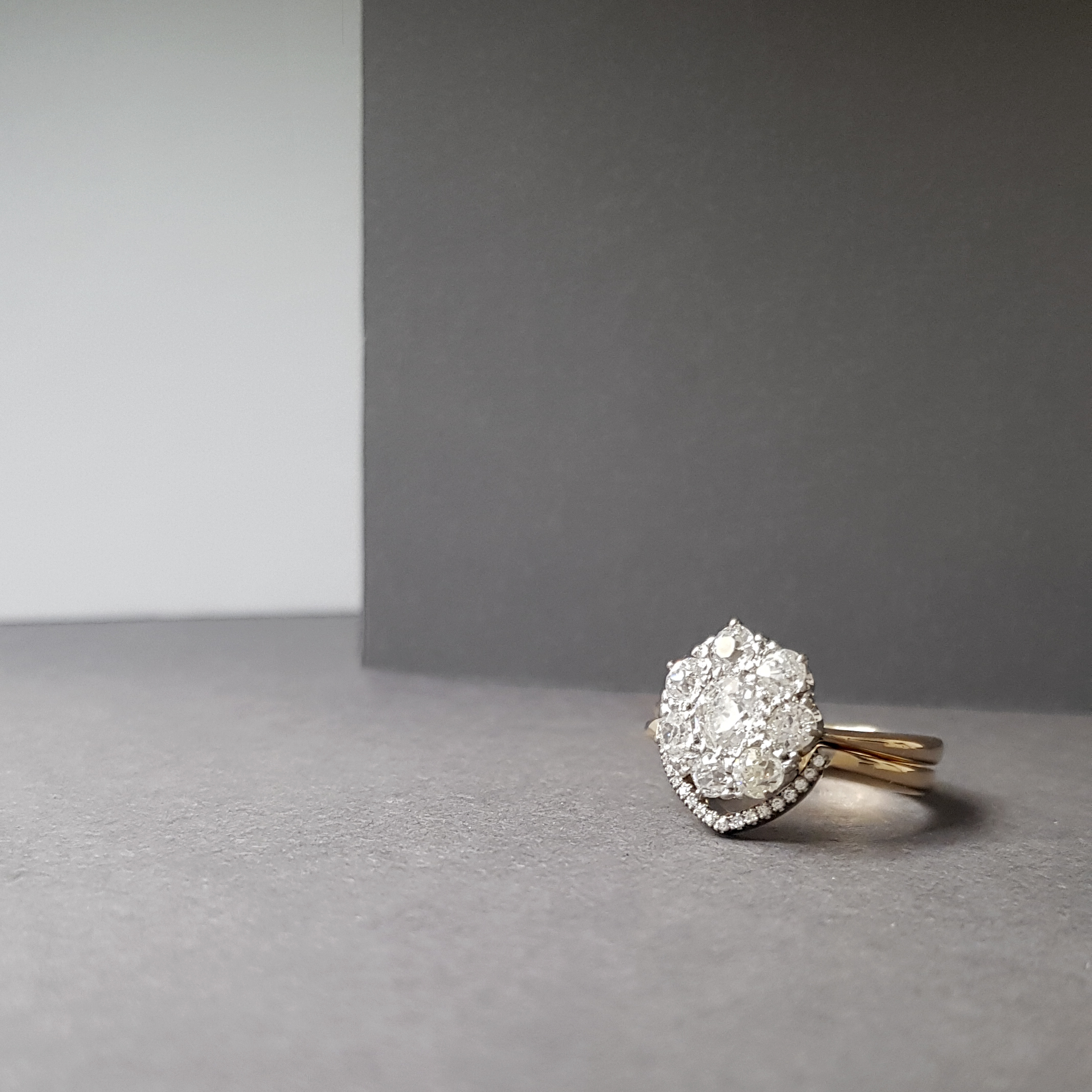Client's vintage diamond cluster engagement ring nestled on top of bespoke V-shaped wedding ring.