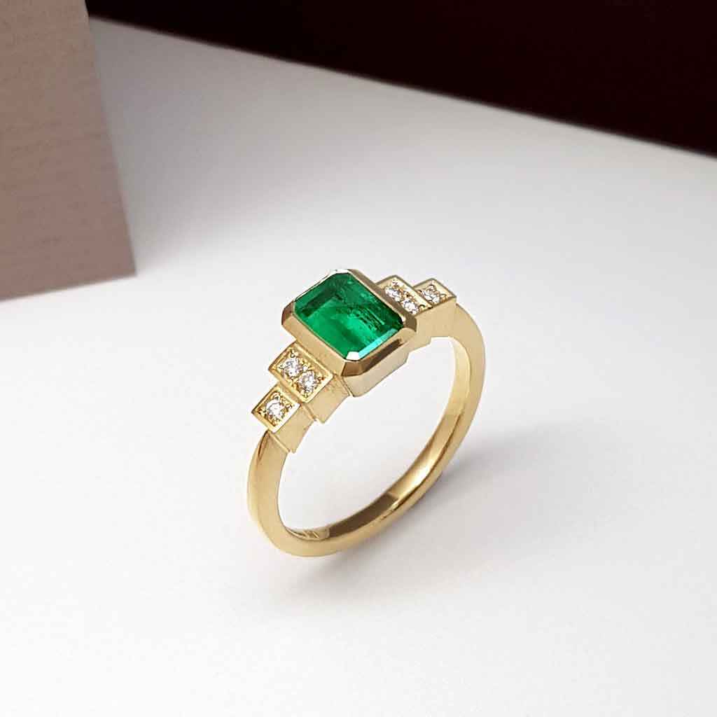 Emerald and diamond engagement ring standing upright on a white, black and grey background..