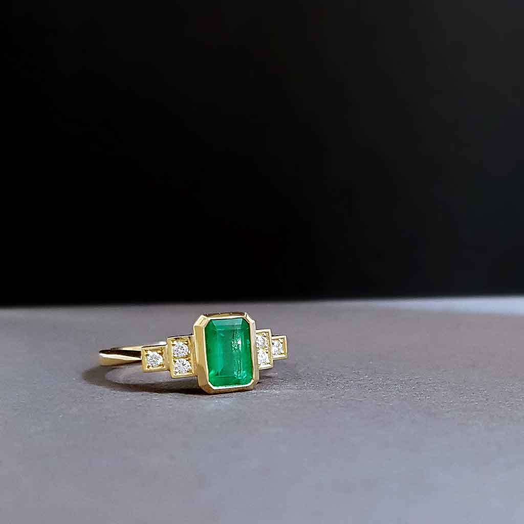 Front view of Emerald and diamond engagement ring on black background.