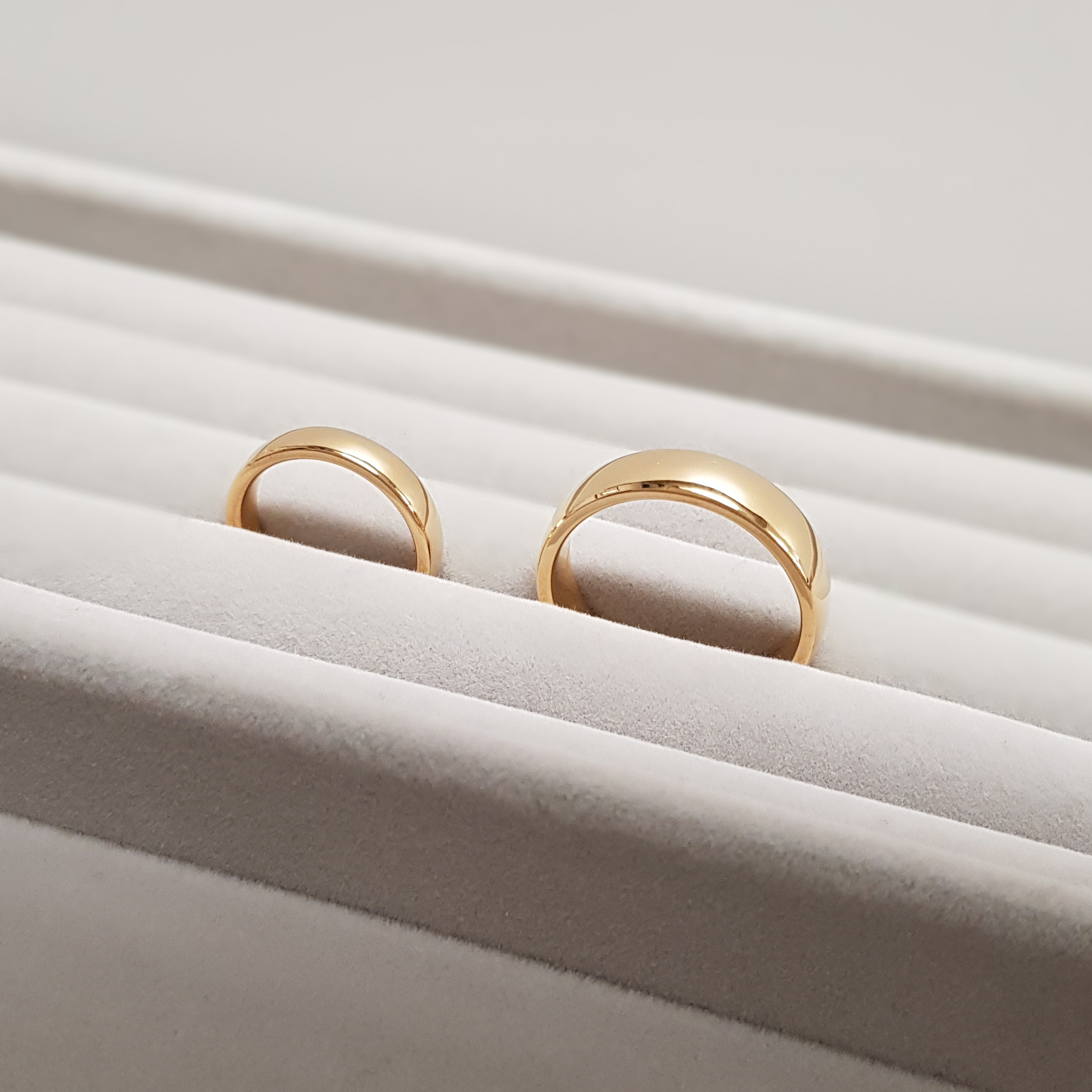 A pair of 22k wedding rings on grey velvet jeweller's display tray.