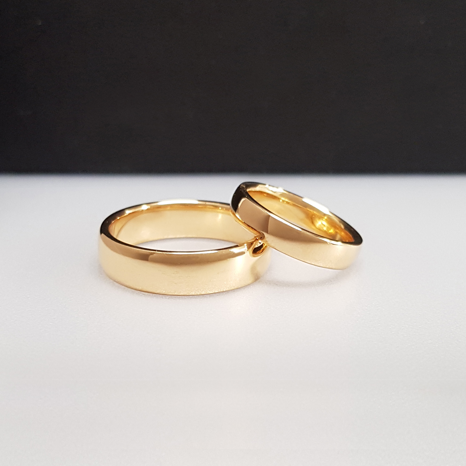 A pair of 22k wedding rings on a white surface with a black background.