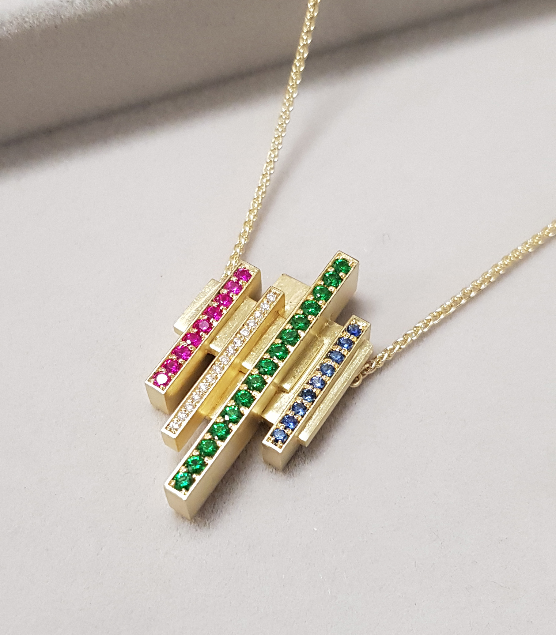 Yellow gold pendant on a spiga chain with diamonds, rubies, sapphires, and tsavorites on a grey background.
