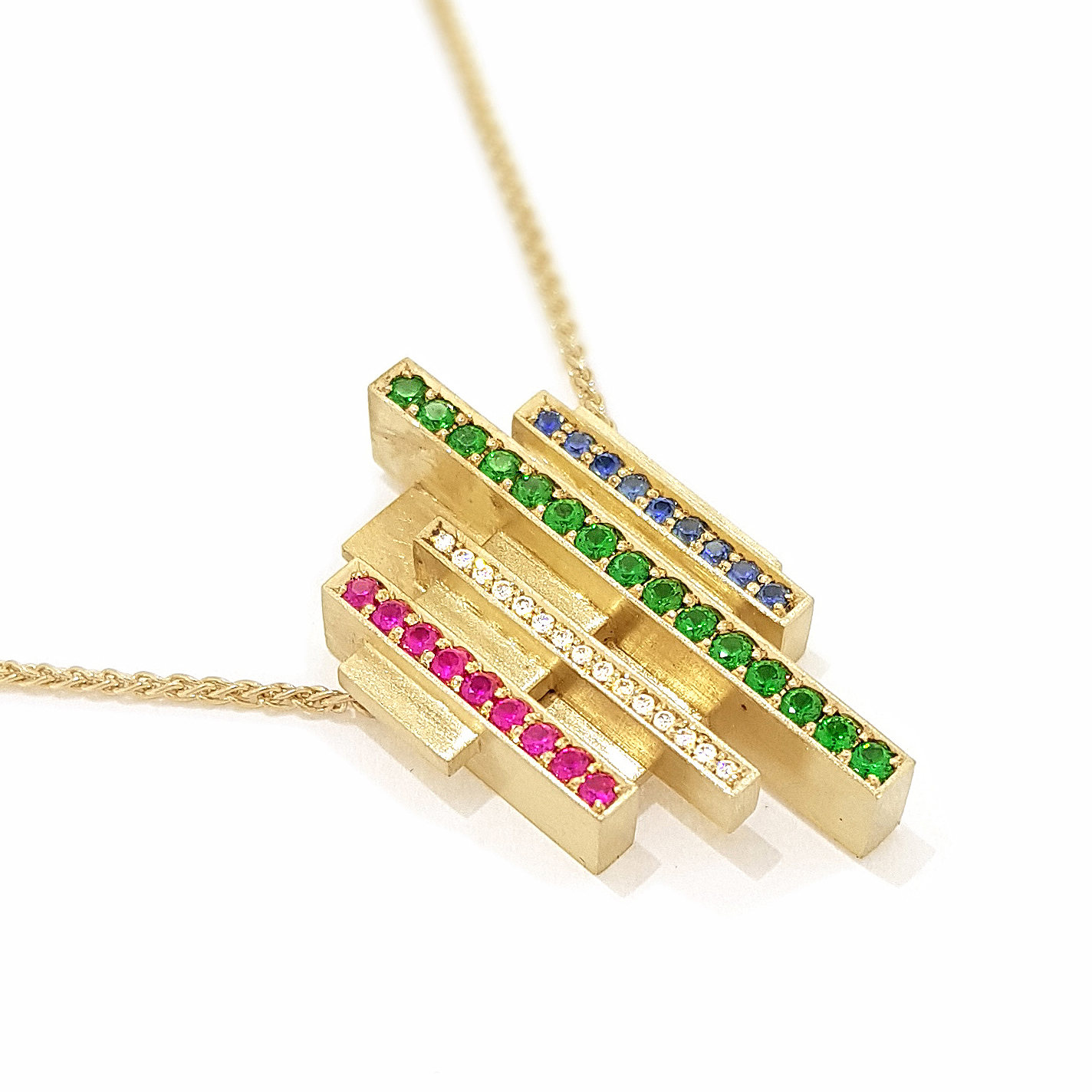 Yellow gold pendant on a spiga chain with diamonds, rubies, sapphires, and tsavorites on a white background.