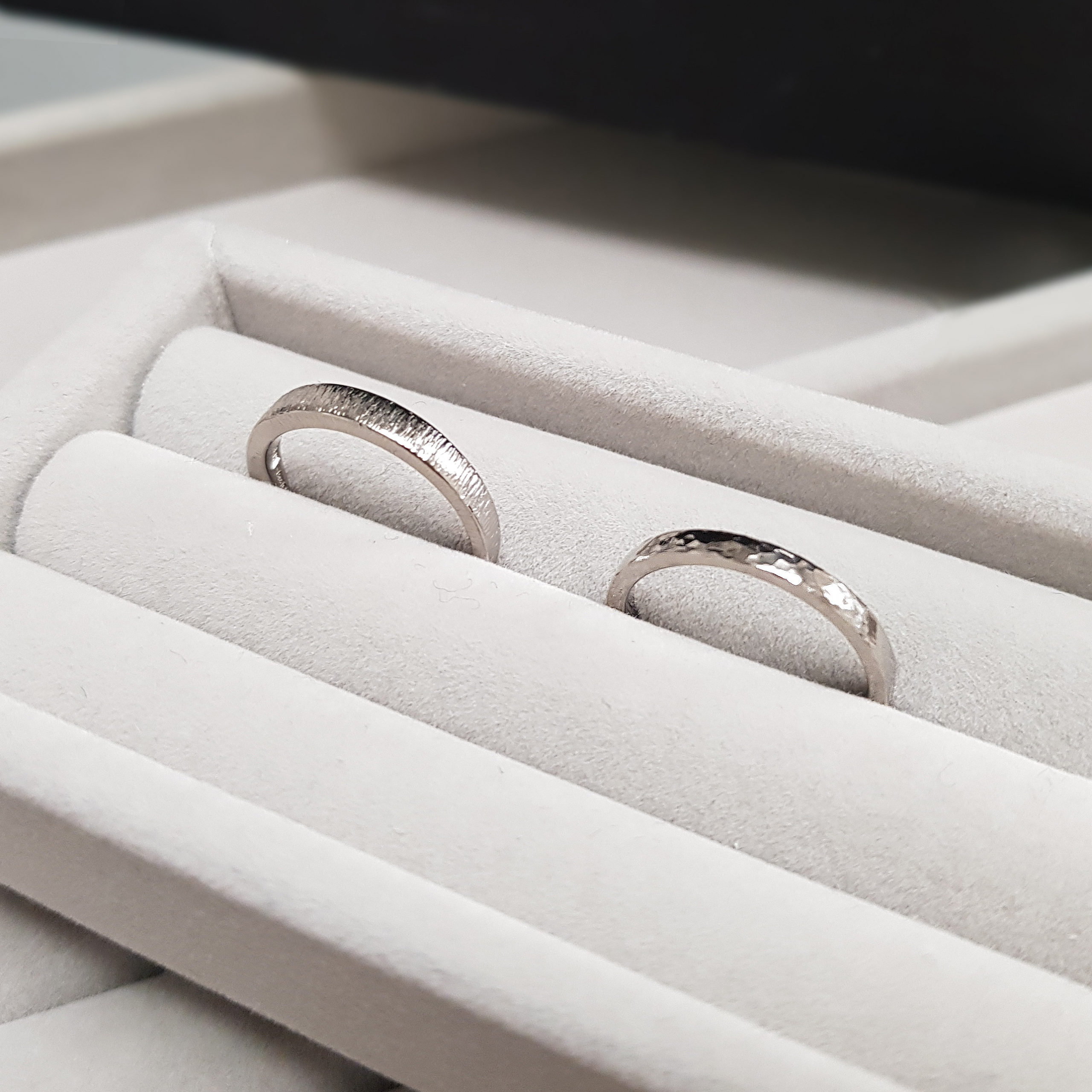 Two hammered wedding rings with hammered finishes positioned in a grey velvet ring tray.