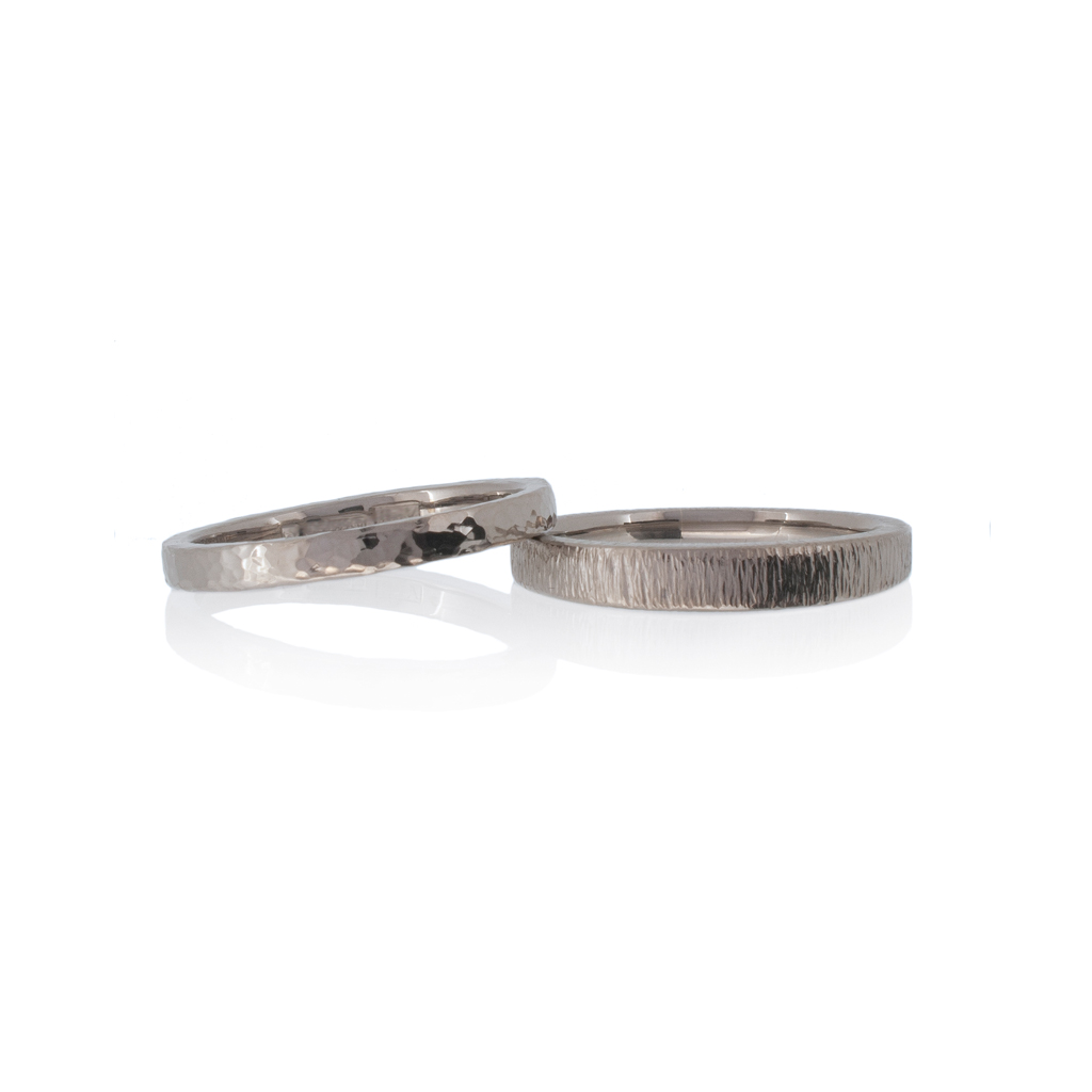 Two hammered wedding rings with hammered finishes on a white background.