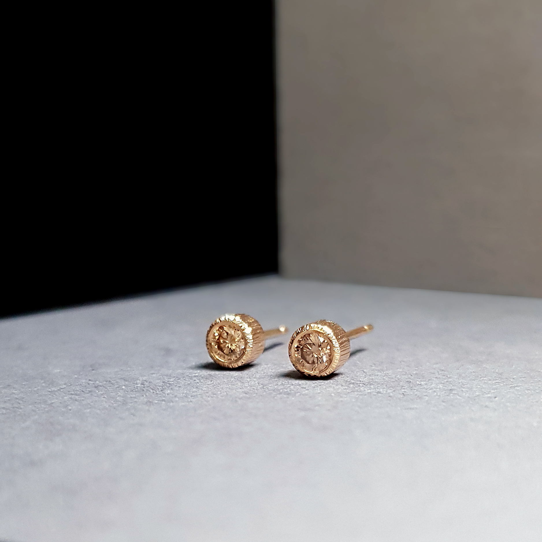 Champagne diamond earrings in 18k rose gold set against a colour block background of black and grey.