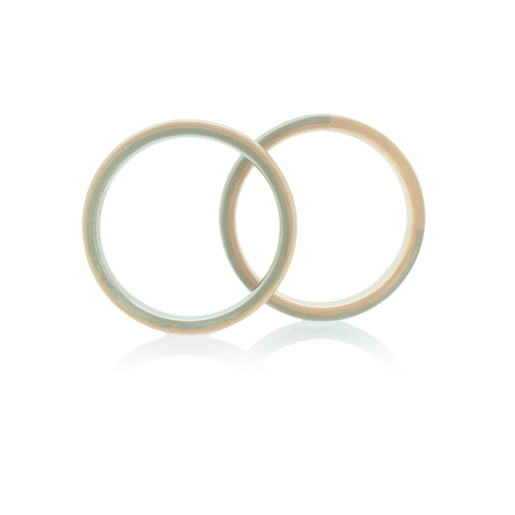Two wedding rings in rose and white gold standing upright on a white background.