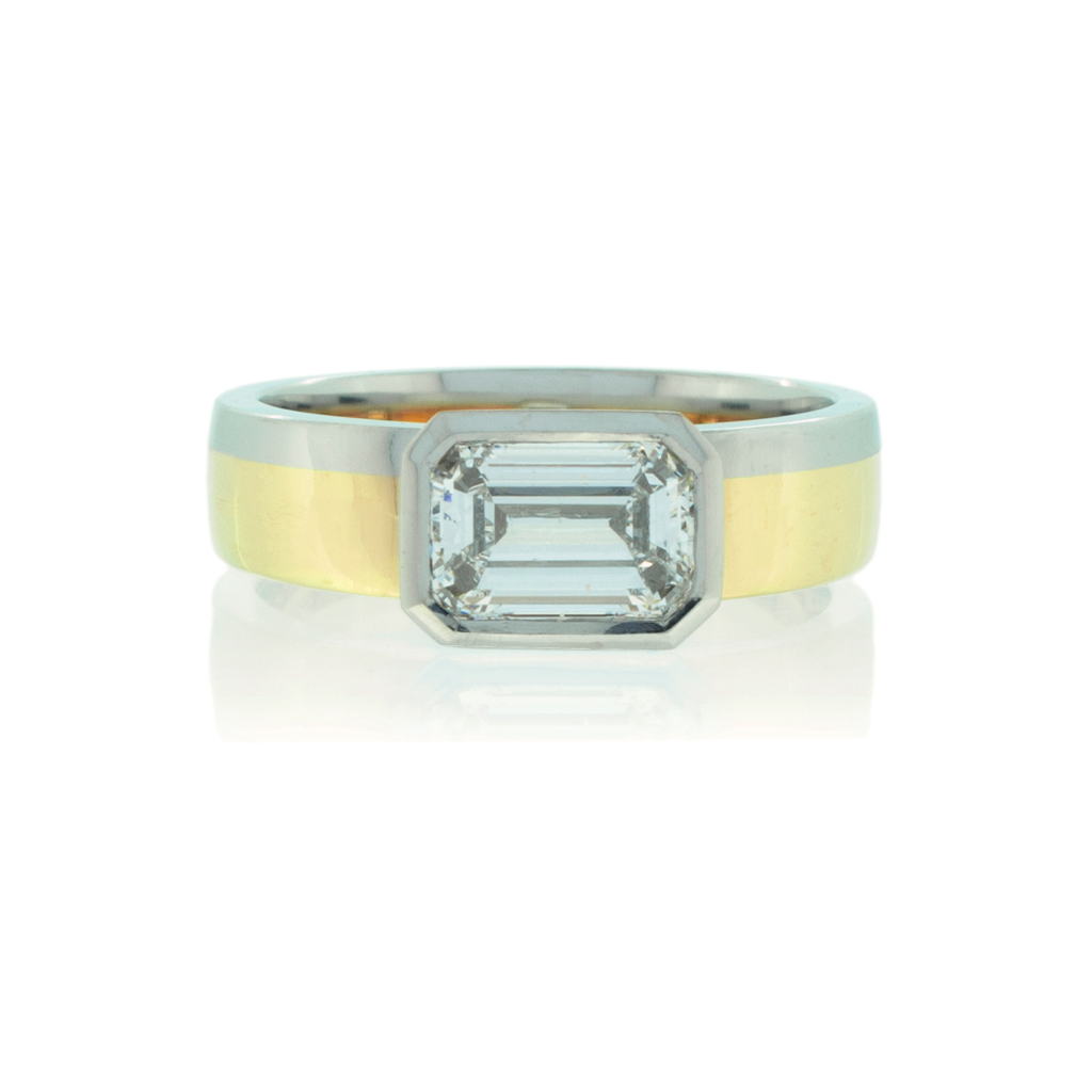 Two tone wedding band made with platinum and gold and horizontally set emerald cut diamond