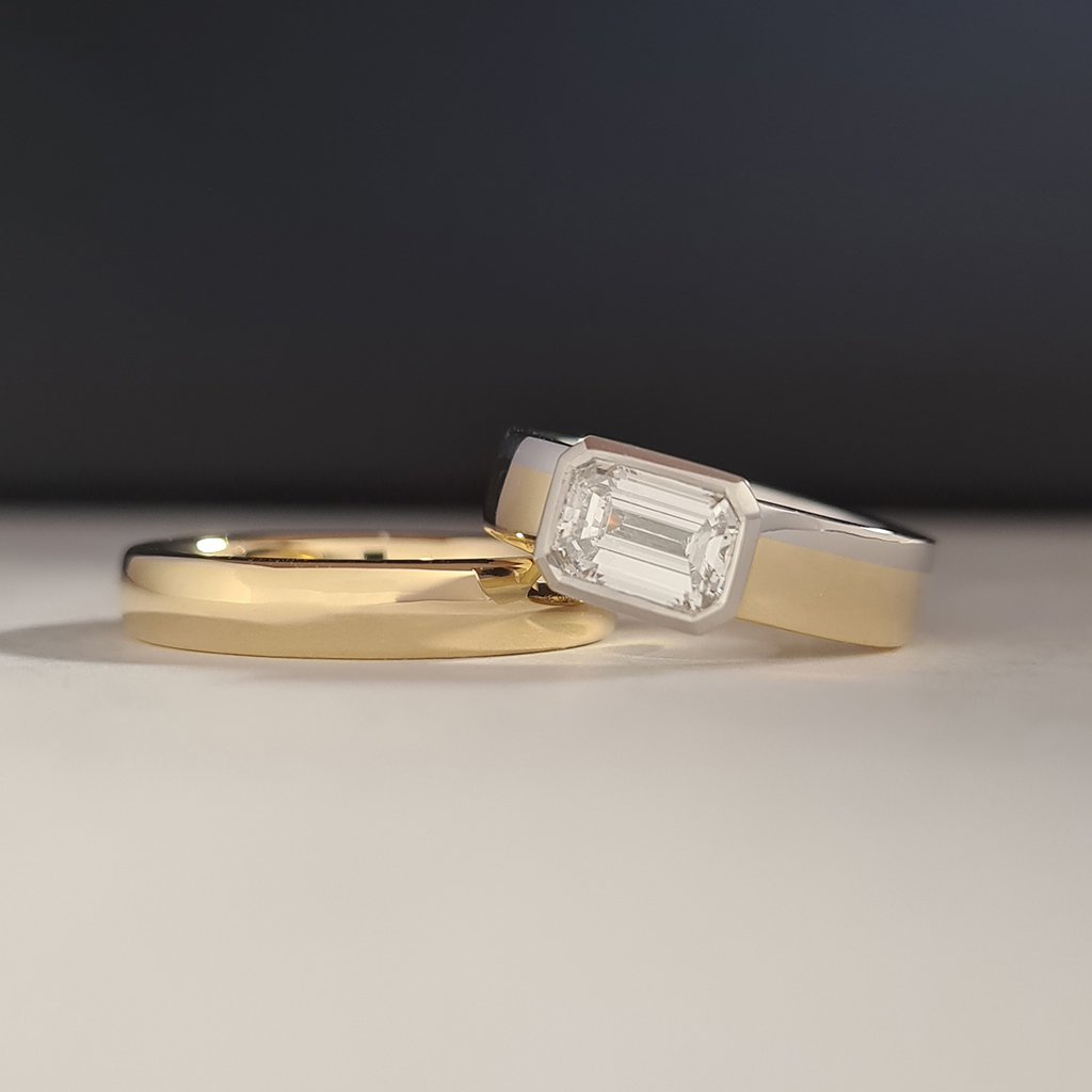Two tone engagement ring in platinum and gold leaning on a yellow gold men's wedding band.
