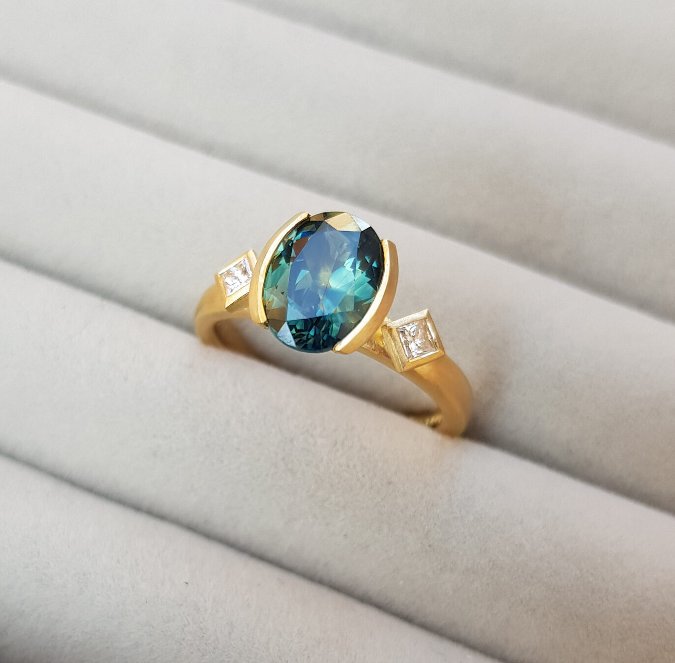 Bespoke ethical engagement ring with large teal blue, parti-sapphire and two diamonds flanked by two diamonds on a gold band in a grey ring tray.