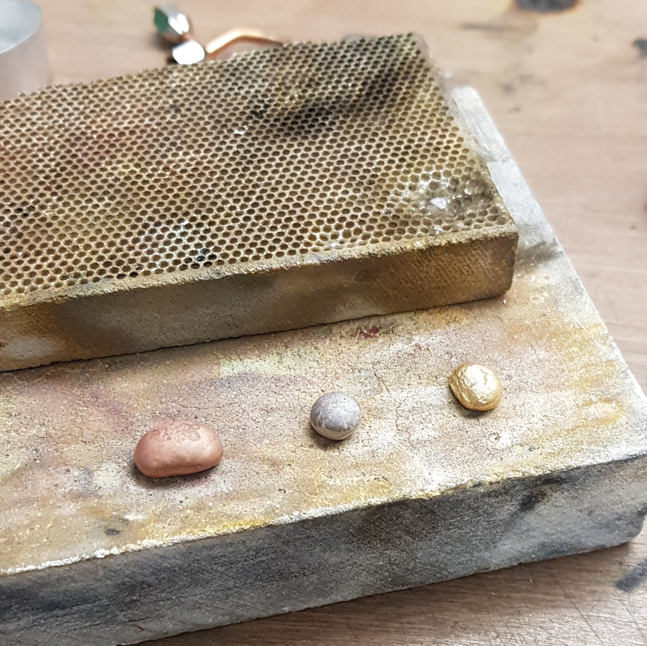 Three ingots of white, red, and yellow gold on a soldering block in the workshop.