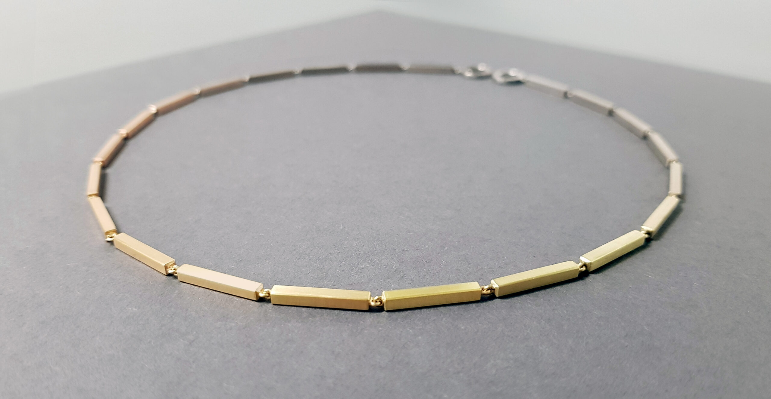 A gold necklace made of interlinking gold bars creating a gradient of colour, laid on a grey background