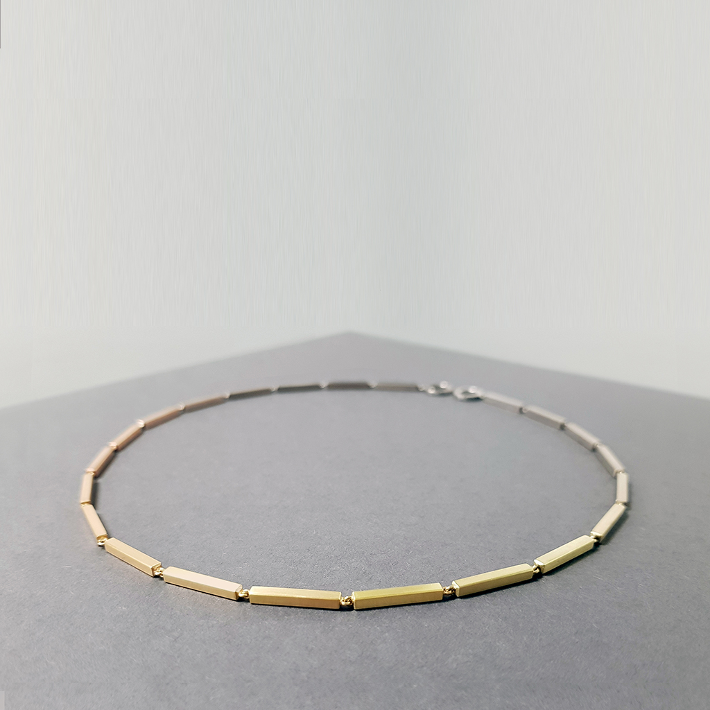 A gold necklace made of solid gold bars creating a gradiant of colour, laid on a grey background