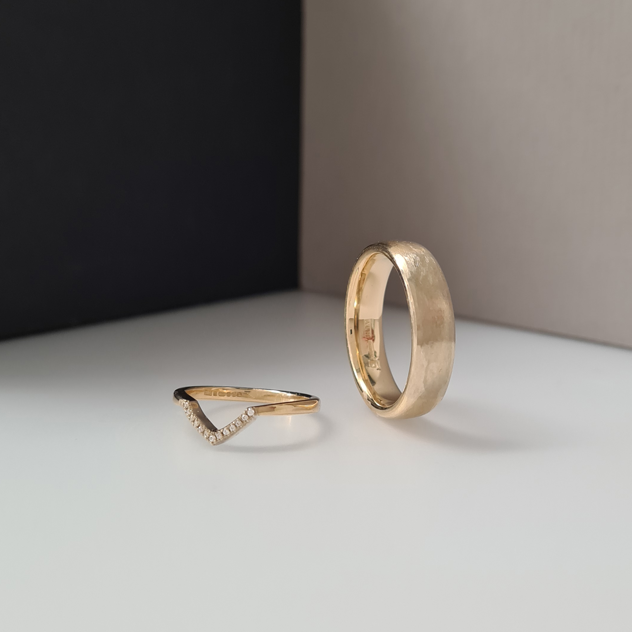 Woman's wedding ring with a V-shaped detail set with diamonds resting on a man's ring on a color block background of white, grey and black.